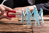 Businessperson's Hand Holding Red Horseshoe Magnet Attracting Paper Cut Out Figures On Wooden Desk