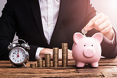 A Businessperson's Hand Putting Coin In Piggybank Besides Alarm Clock On Desk