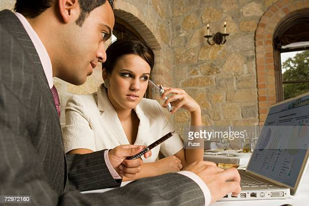 Businesspersons looking at laptop in restaurant