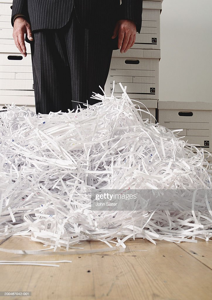 Businesssman by shredded paper, low section