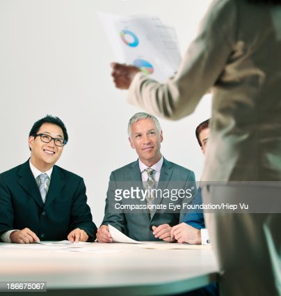 Businesswoman addressing colleagues at table : Stock Photo