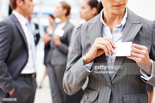 Businesswoman adjusts her name tag, others network
