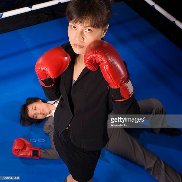 Businesswoman after knocking down her opponent in a boxing ring