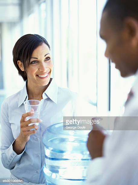 businesswoman and a businessman talking and drinking water in an office