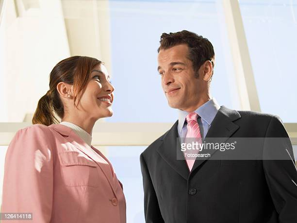Businesswoman and businessman looking each other (low angle view)