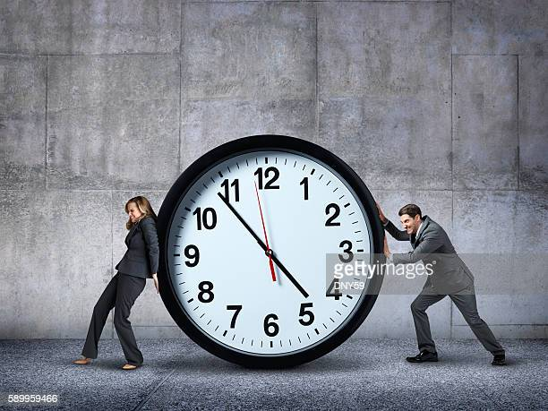 Businesswoman And Businessman Pushing In Opposite Directions Against A Clock
