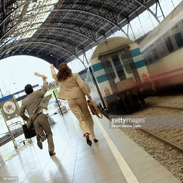 Businesswoman and Businessman Running after Departing Train