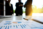 Businesswoman and Businessman stand in out of focus graph chart on the table concept business consult