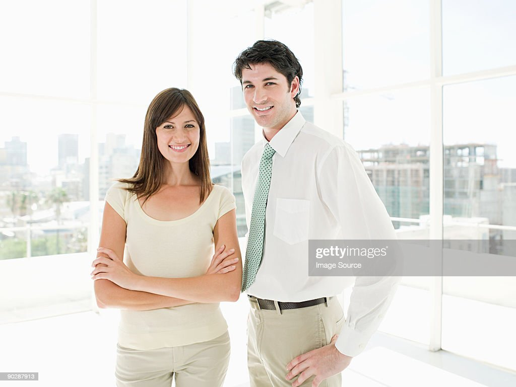 Businesswoman and businessman standing in office : Stock Photo