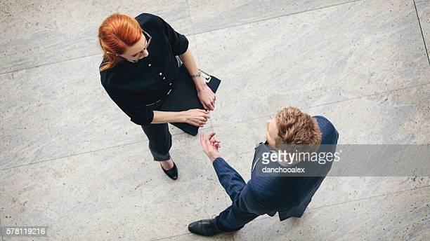Geschäftsfrau und Geschäftsmann steht im die Halle und reden