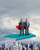 A businesswoman and a businessman each wearing a red cape stand proudly and attentively as they stand with their hands on their hips on a large green arrow that flies above a large urban skyline.