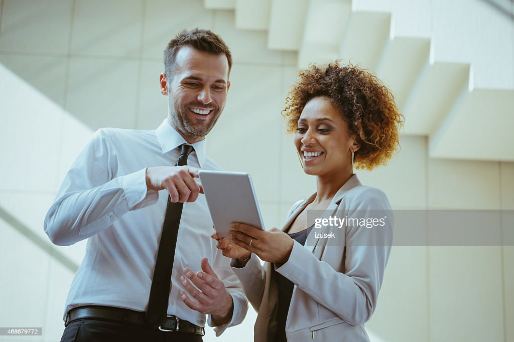 Businesswoman and businessman using a digital tablet together