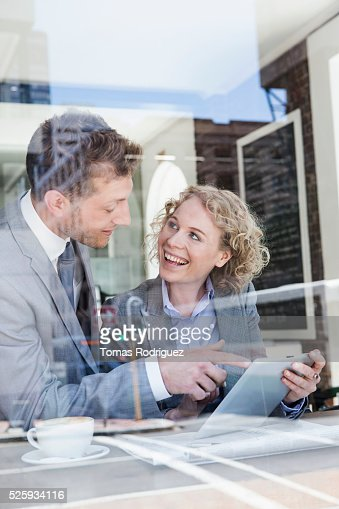 Businesswoman and businessman using tablet PC in cafe : ストックフォト