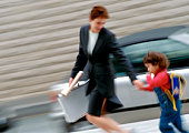 Businesswoman and child holding hands, blurred motion