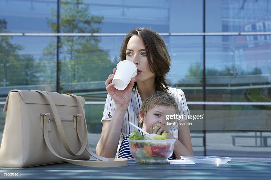 Businesswoman and her child eating lunch together outside. : Stock Photo