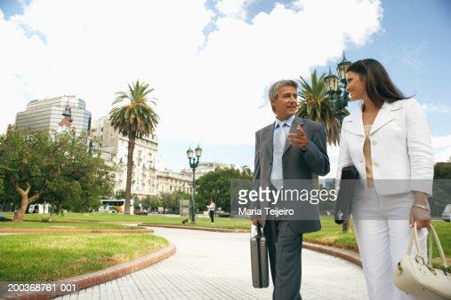 Businesswoman and man walking in park talking
