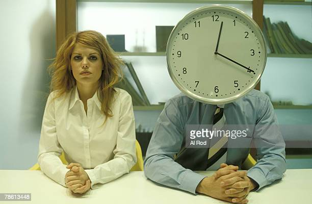 Businesswoman and man with clock head