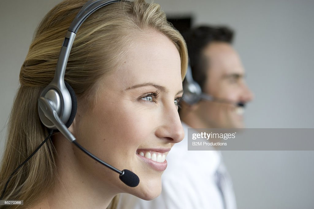 Businesswoman and man with headsets : Stock Photo