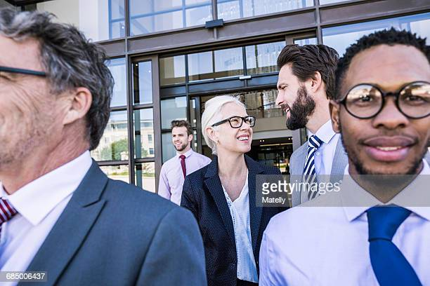 Businesswoman and men leaving office building