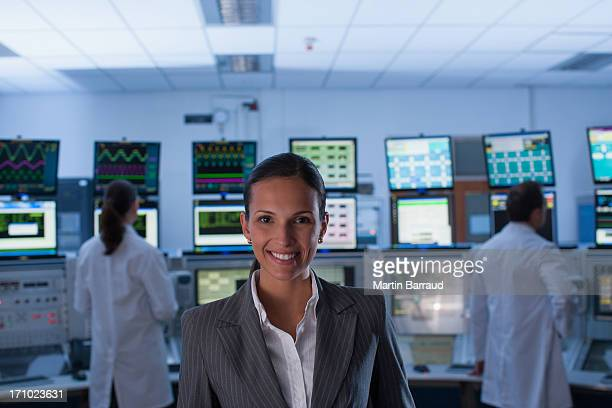 Businesswoman and scientists standing in control room