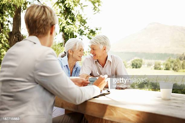Businesswoman and Senior Couple Sitting at Rustic Outdoor Table