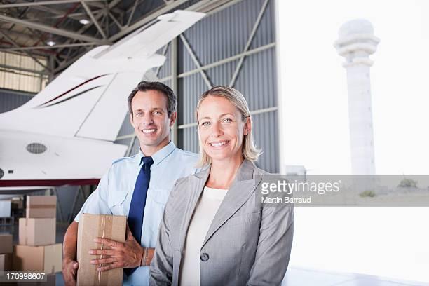 Geschäftsfrau und Arbeiter stehend in hangar