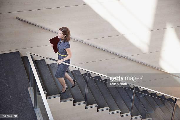 Femme d'affaires grimper bureau escalier