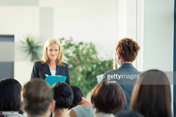 Businesswoman asking a question during seminar