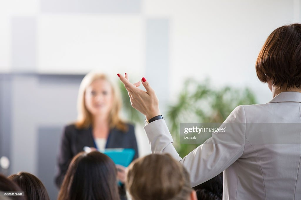 Businesswoman asking a question during seminar : Stock Photo
