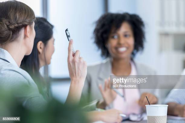 Businesswoman asks question during meeting