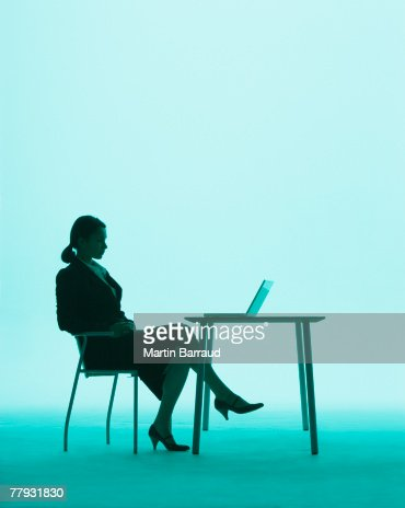 Businesswoman at a table on a laptop : Stock Photo