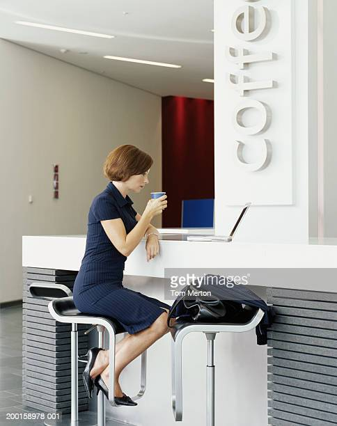 Businesswoman at cafe counter, looking at laptop, profile