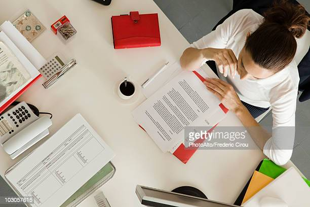 Businesswoman at desk busy with paperwork, overhead view