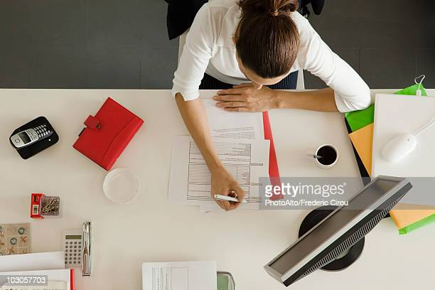 Businesswoman at desk busy with paperwork