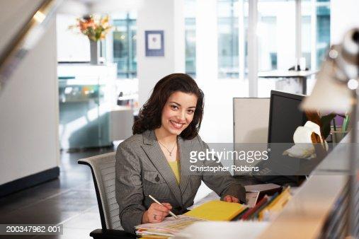 Businesswoman at desk, smiling, portrait