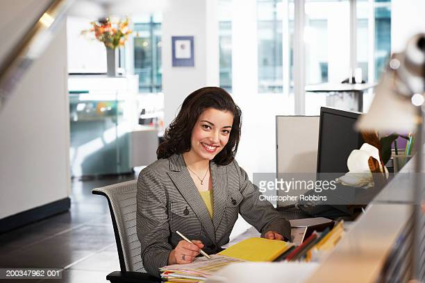Businesswoman at desk, smiling, portrait