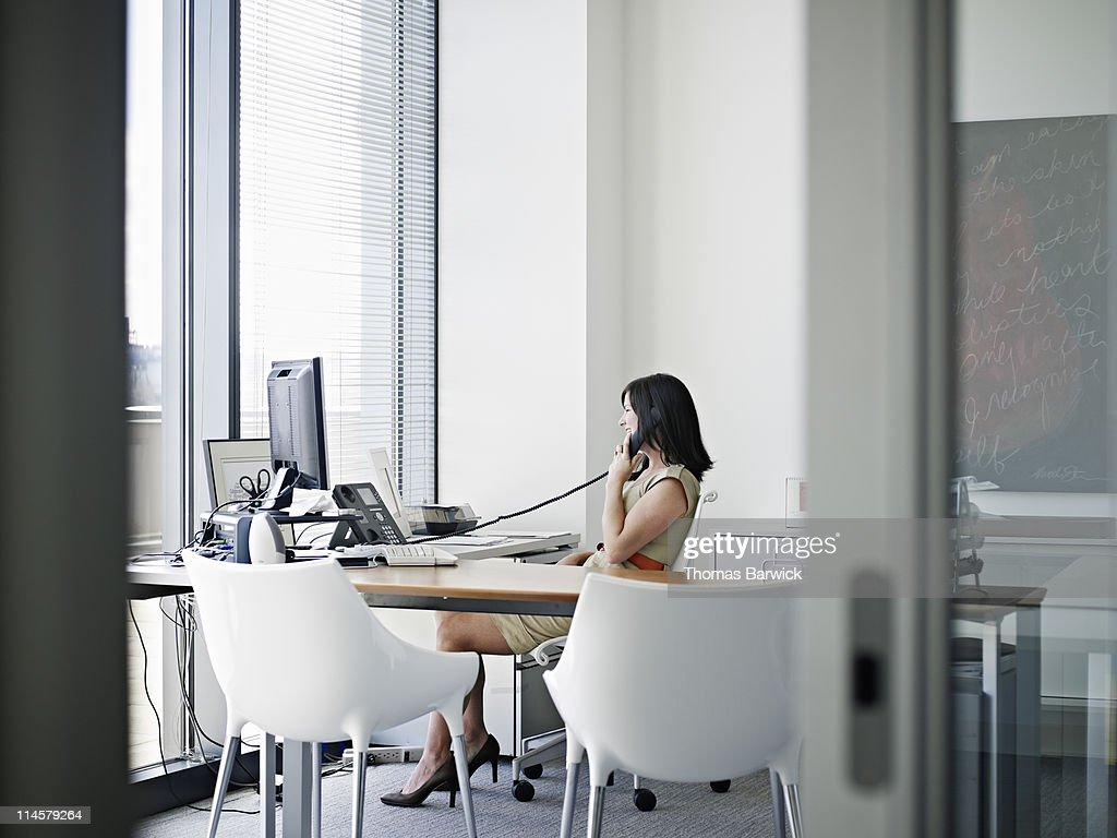 Businesswoman at desk talking on phone smiling : Stock Photo