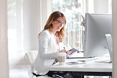 Portrait of beautiful businesswoman sitting at office and writing to her diary while working online.
