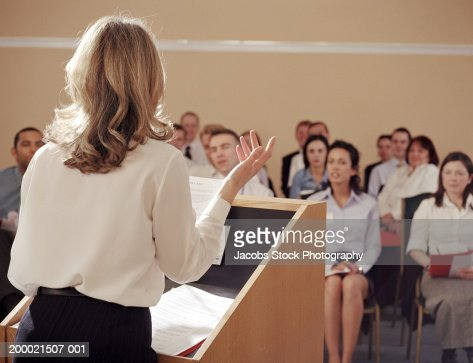 Businesswoman at podium addressing colleagues, rear view : ストックフォト