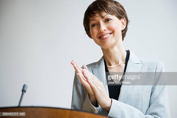 Businesswoman at podium clapping