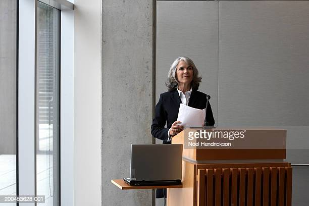 Businesswoman at podium holding document with laptop