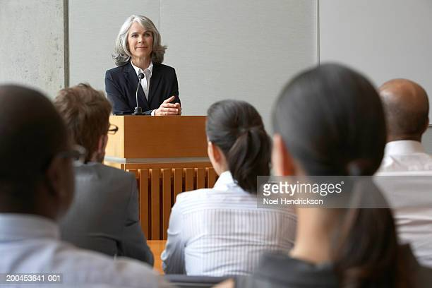 Businesswoman at podium talking to colleagues