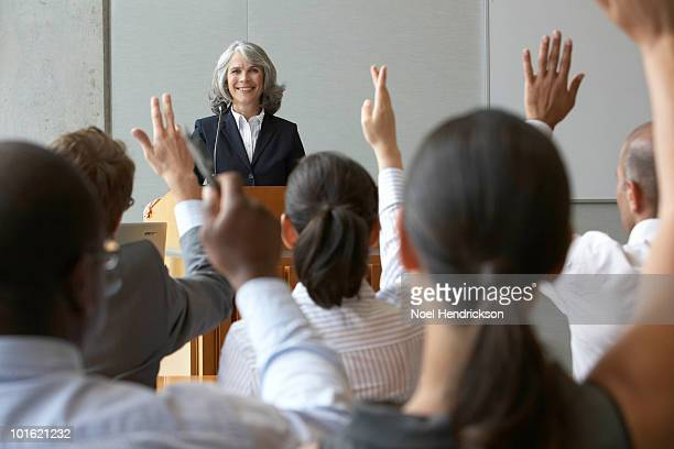 Businesswoman at podium with colleauges raising their hands, smiling