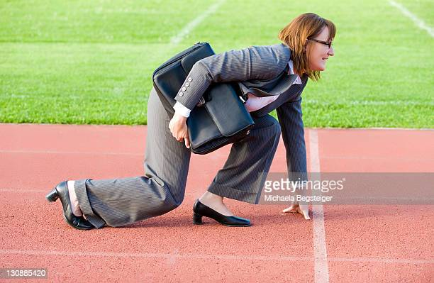 Businesswoman at starting line of a running track, symbolic of carreer start