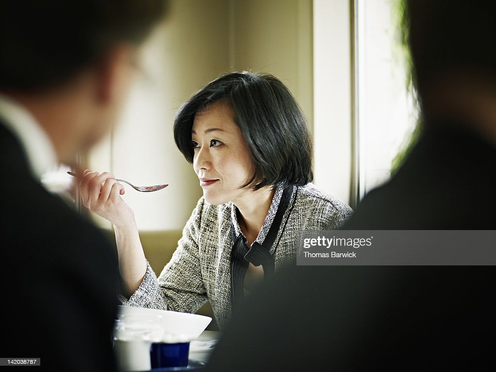 Businesswoman at table in restaurant eating : Stock Photo