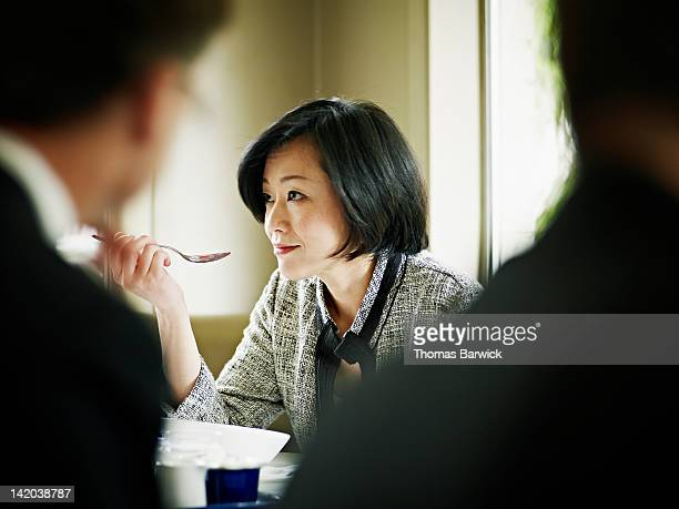 Businesswoman at table in restaurant eating