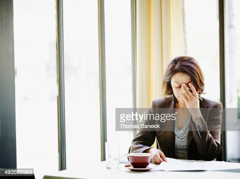 Businesswoman at table with head resting on hand