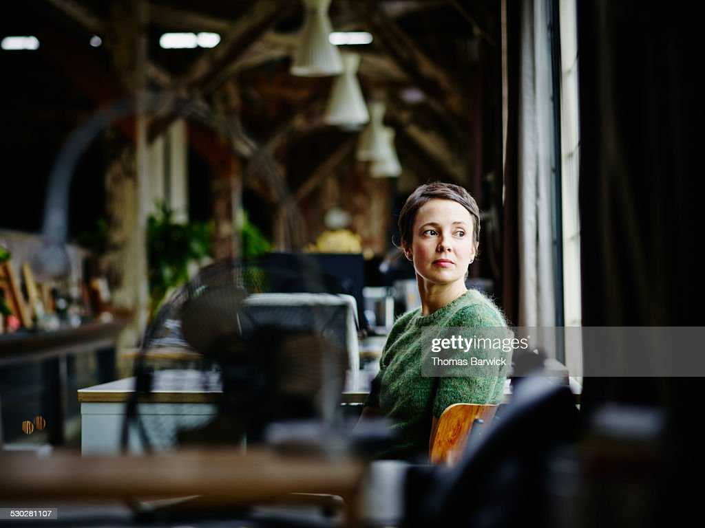 Businesswoman at workstation looking out window : Stock Photo