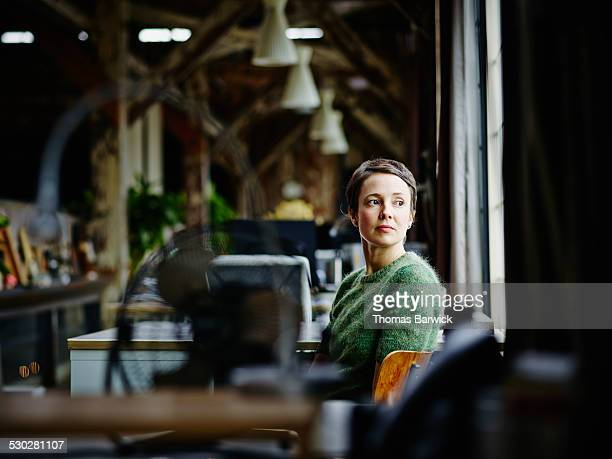 Businesswoman at workstation looking out window