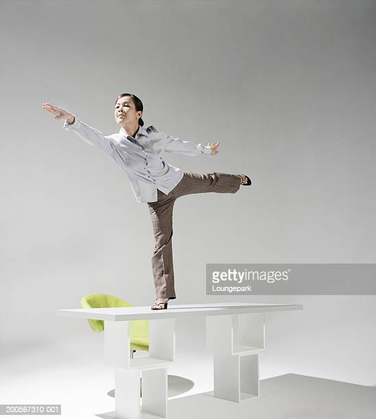 Businesswoman balancing on desk
